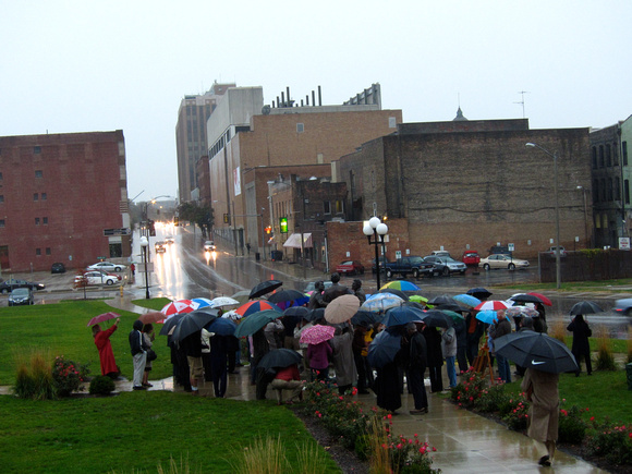"Guests with umbrellas gather around ""Convergence of Purpose"" during the dedication October 23, 2010."
