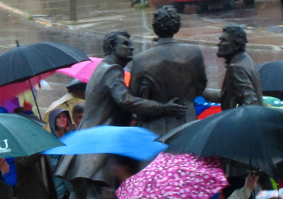 The figures in the statuary grouping appear amid the umbrellas of the audience after the unveiling of the work October 23, 2010.